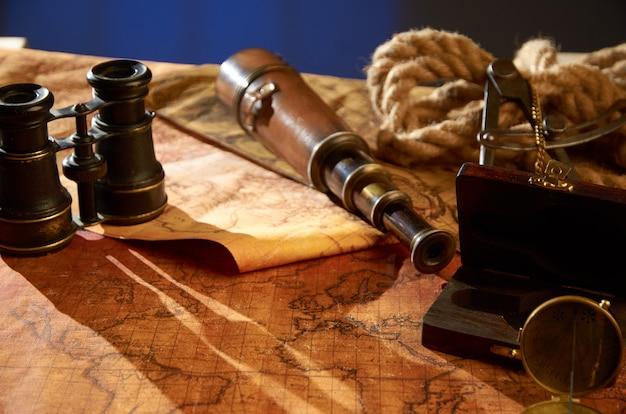Telescopio con brújula y cuerda de cáñamo en el mapa antiguo