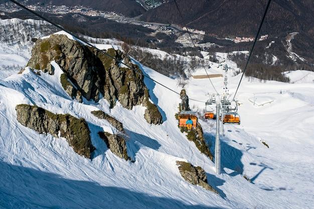 Un telesilla en las montañas con esquiadores y practicantes de snowboard en invierno