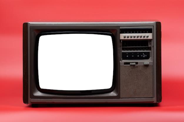 Televisión vintage con pantalla recortada sobre fondo rojo.
