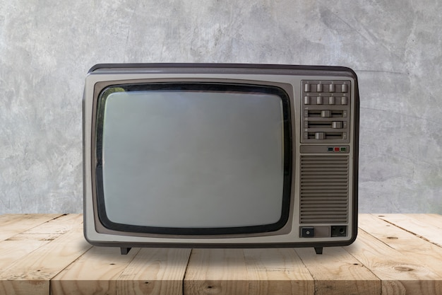 Televisión del vintage en textura y fondo de madera de la pared de la tabla y del cemento.