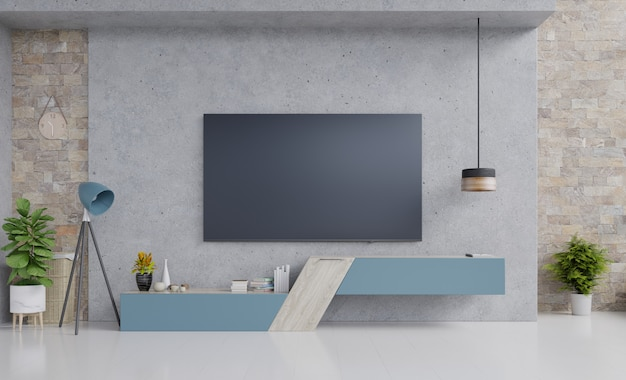 Televisor en el gabinete de diseño azul en la moderna sala de estar con lámpara, flor y planta en la pared de cemento.