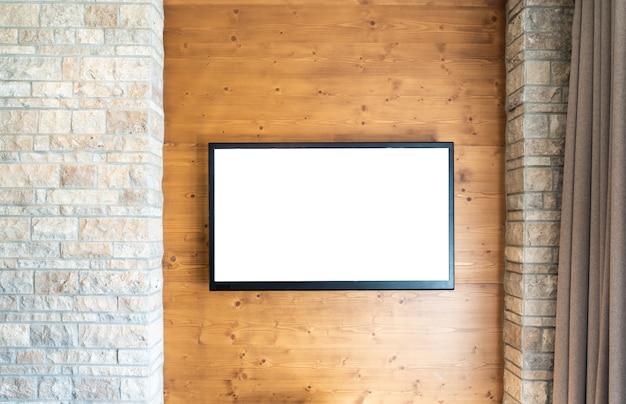 Televisor de pantalla plana moderno en blanco en la pared de ladrillo y madera con espacio de copia