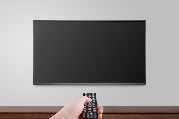 Televisor en pared blanca con mando a distancia