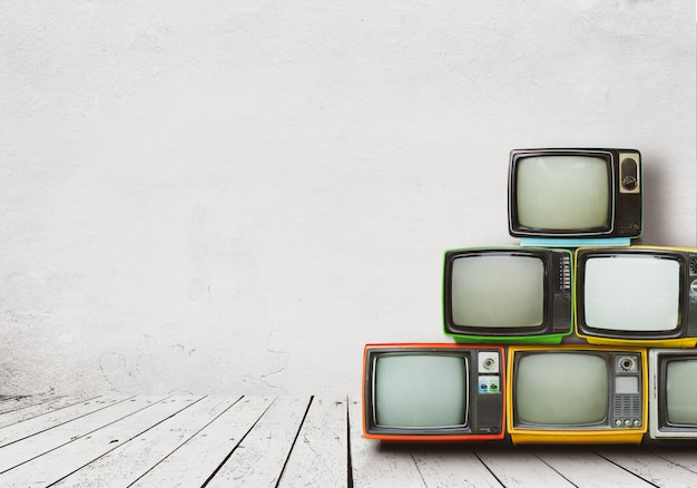Televisores retro se apilan en el piso de la habitación vieja con pared blanca