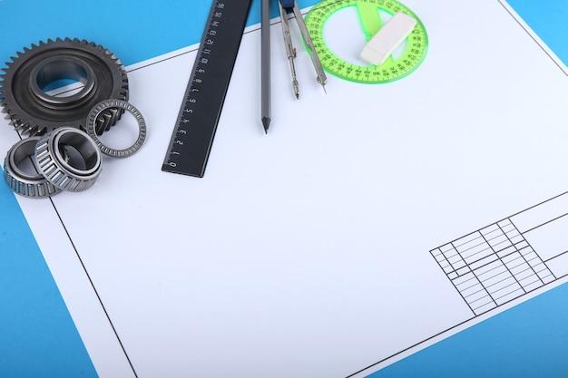 Telón de fondo con accesorios de dibujo, papel de dibujo y engranajes metálicos con espacio de copia