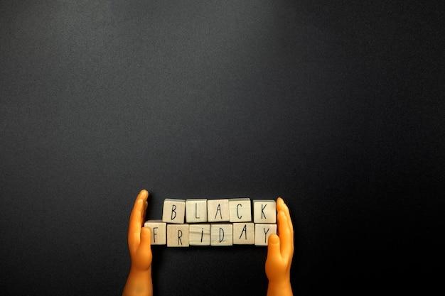 Tema black friday: manos de piel oscura sosteniendo un texto con black friday sobre fondo negro, concepto de venta con espacio de copia