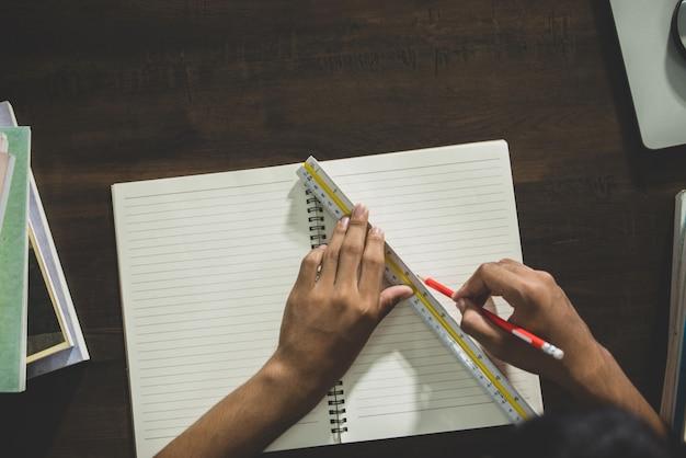 Tema educativo: primer plano escritura del alumno en un aula.
