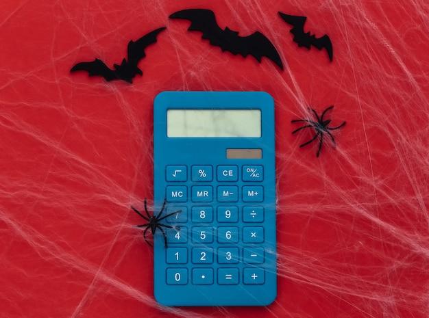 Tema de halloween. calculadora en rojo con telarañas, murciélagos y arañas.