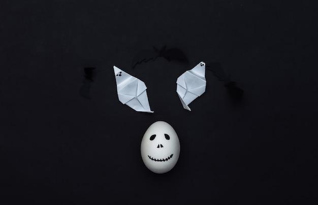 Tema de halloween. huevo con cara de fantasma aterrador dibujado a mano y fantasma sobre fondo negro