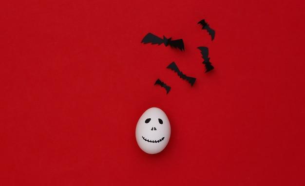 Tema de halloween. huevos con cara de fantasma aterrador dibujado a mano y murciélagos sobre fondo rojo