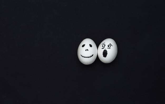 Tema de halloween. huevos con cara de fantasma aterrador dibujado a mano sobre fondo negro