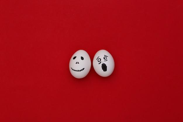 Tema de halloween. huevos con cara de fantasma aterrador dibujado a mano sobre fondo rojo