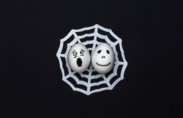 Tema de halloween. huevos con cara de fantasma aterrador dibujado a mano con web sobre fondo negro