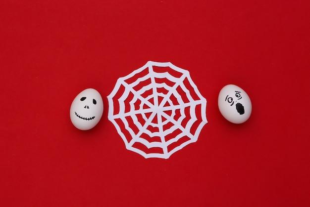 Tema de halloween. huevos con cara de fantasma aterrador dibujado a mano con web sobre fondo rojo