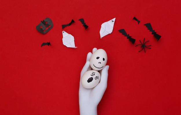 Tema de halloween. mano de maniquí sosteniendo huevos con cara de fantasma aterrador dibujado a mano y murciélagos sobre fondo rojo