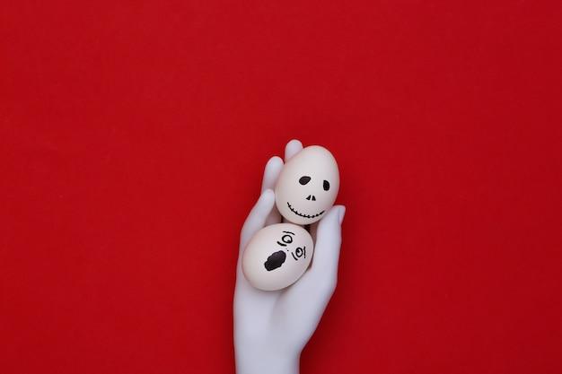 Tema de halloween. mano de maniquí sosteniendo huevos con cara de fantasma aterrador dibujado a mano sobre fondo rojo