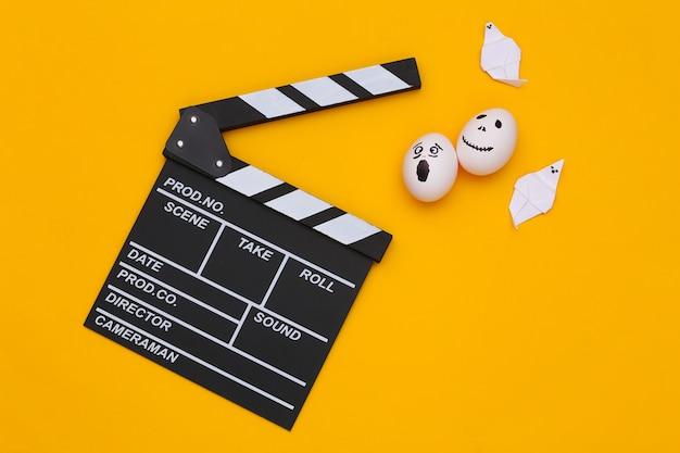 Tema de halloween. tablero de azote de película y huevo con cara de fantasma aterrador dibujado a mano sobre fondo amarillo