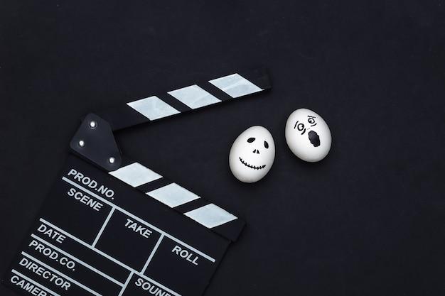 Tema de halloween. tablero de azote de película y huevo con cara de fantasma aterrador dibujado a mano sobre fondo negro