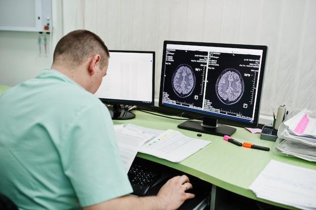 Tema médico. médico en la oficina de resonancia magnética en el centro de diagnóstico en el hospital, sentado cerca de monitores de computadora con cerebro humano.