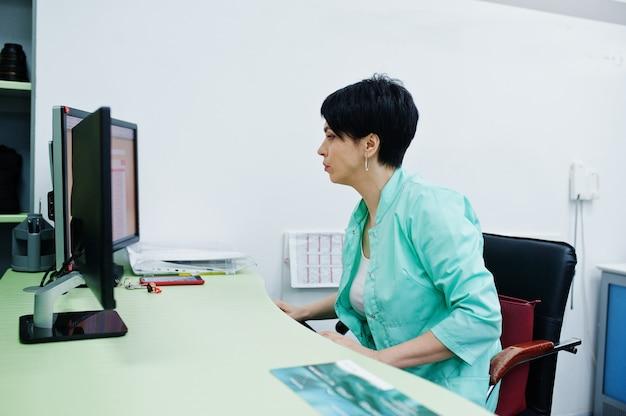 Tema médico. médico en la oficina de resonancia magnética en el centro de diagnóstico en el hospital, sentado cerca de monitores de computadora.