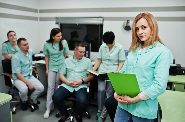 Tema médico. retrato de doctora con portapapeles contra grupo de médicos reunidos en la oficina de resonancia magnética en el centro de diagnóstico en el hospital.