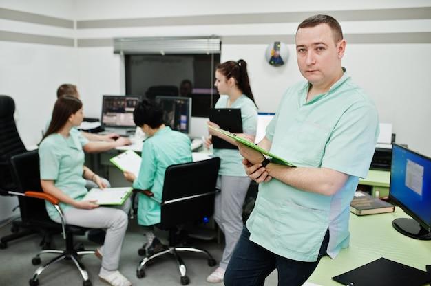 Tema médico. retrato de médico masculino con portapapeles contra grupo de médicos reunidos en la oficina de resonancia magnética en el centro de diagnóstico en el hospital.