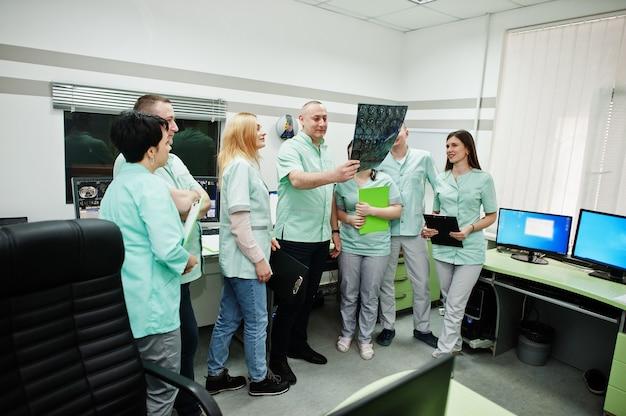 Tema médico sala de observación con tomógrafo computarizado. el grupo de médicos reunidos en la oficina de resonancia magnética y mirando radiografías en el centro de diagnóstico en el hospital.
