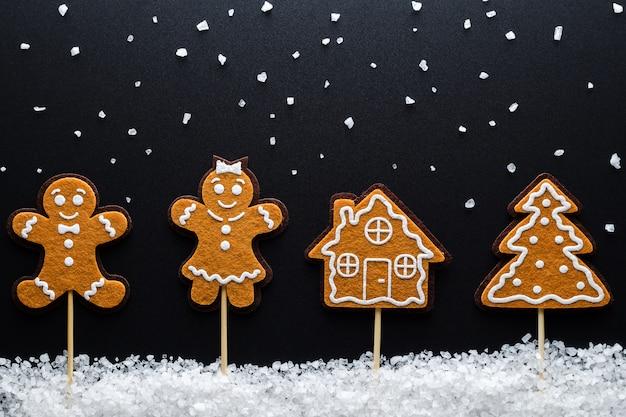 Tema de navidad. hombres de jengibre (hombre, mujer) en la nieve (sal marina grande) junto a la casa y el árbol. de cerca.