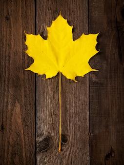 Tema de otoño. hoja amarilla sobre fondo de madera