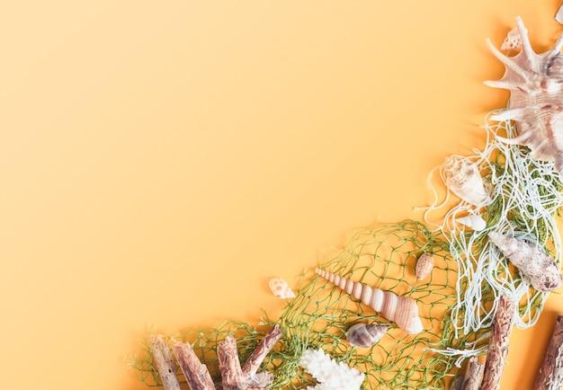 Tema de relajación de vacaciones de verano con conchas marinas, sombrero, gafas de sol y cámara en amarillo