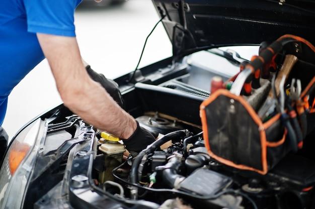 Tema de reparación y mantenimiento de automóviles. mecánico en uniforme trabajando en auto servicio, control de motor.
