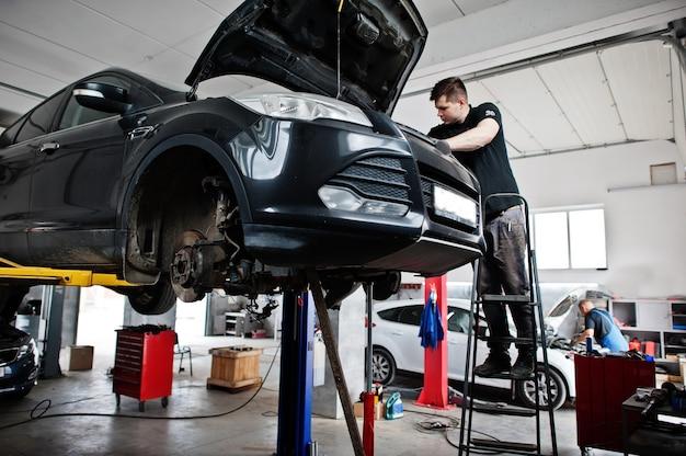 Tema de reparación y mantenimiento de automóviles. mecánico en uniforme trabajando en auto servicio.
