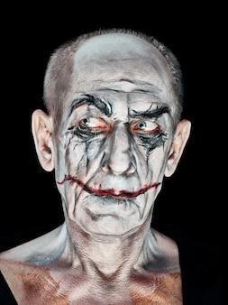 Tema sangriento de halloween: la cara de maníaco loco en estudio oscuro