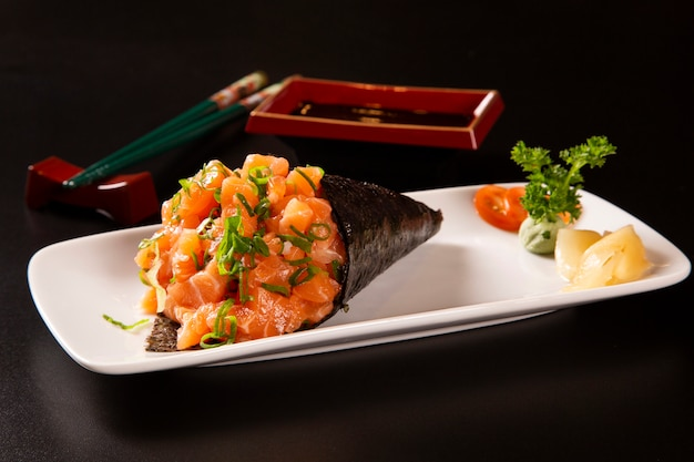 Temaki sushi de salmón en un plato blanco sobre fondo negro.