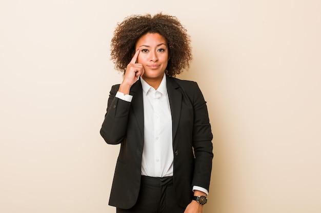 Templo afroamericano de la mujer joven del negocio que señala con el dedo, pensando, centrado en una tarea.
