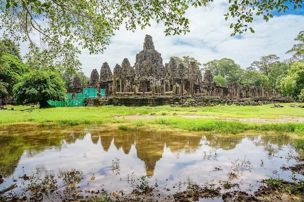 Templo antiguo bayon angkor complejo con caras de piedra en el cielo azul nublado, camboya