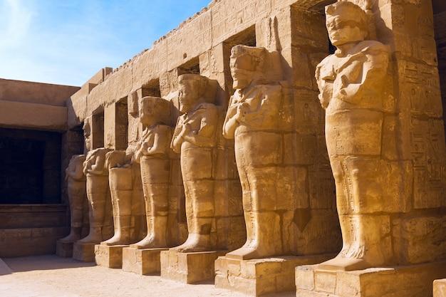Templo de karnak, esculturas colosales del antiguo egipto en el valle del nilo en luxor, jeroglíficos en relieve en la pared