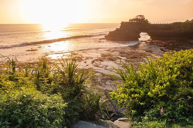 Templo de pura batu bolong en un acantilado de roca con un árbol en la costa al atardecer