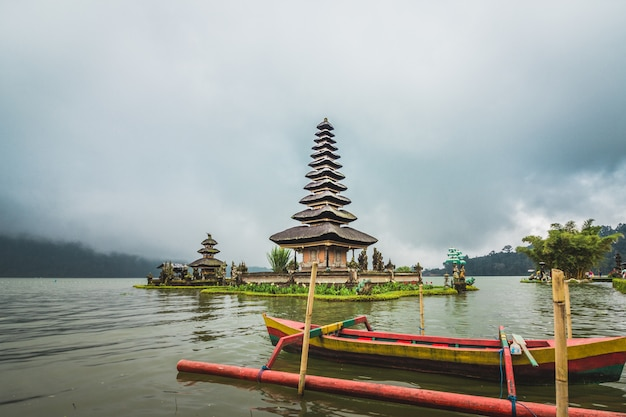 Templo ulun danu beratan en la isla en el lago rodeado de montañas y nubes