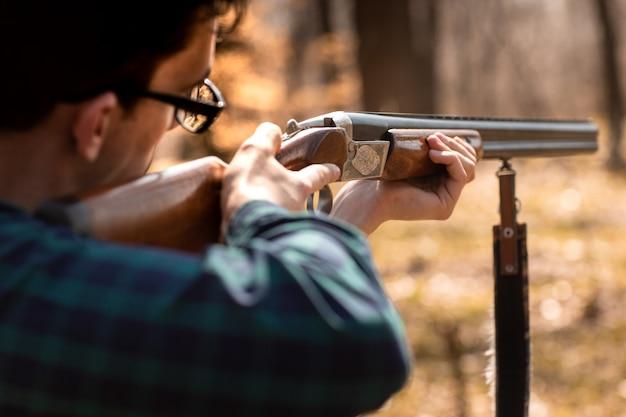 Temporada de caza de otoño. hombre cazador con una pistola. caza en el bosque