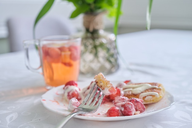 Temporada de fresas, comida y bebida con frutos rojos. comida en la mesa, panqueques de cuajada con fresas y crema agria. té con limón y frutos rojos