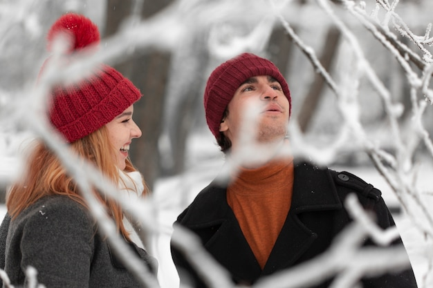 Temporada de invierno cubierto de nieve con pareja tiro medio