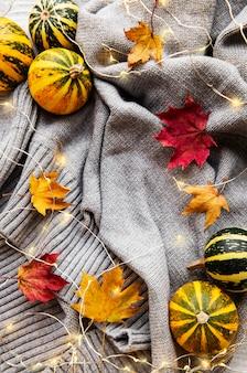 Temporada de otoño vacaciones de acción de gracias. calabazas y un cálido suéter gris con brillantes guirnaldas. ambiente de otoño acogedor. otoño.