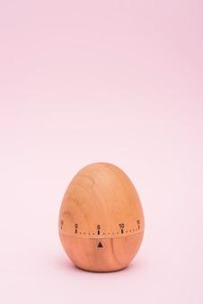 Temporizador de huevo sobre fondo rosa