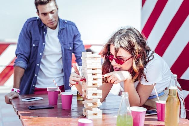 Ten cuidado. encantadora mujer expresando positividad mientras juega al juego de mesa en grupo de sus amigos