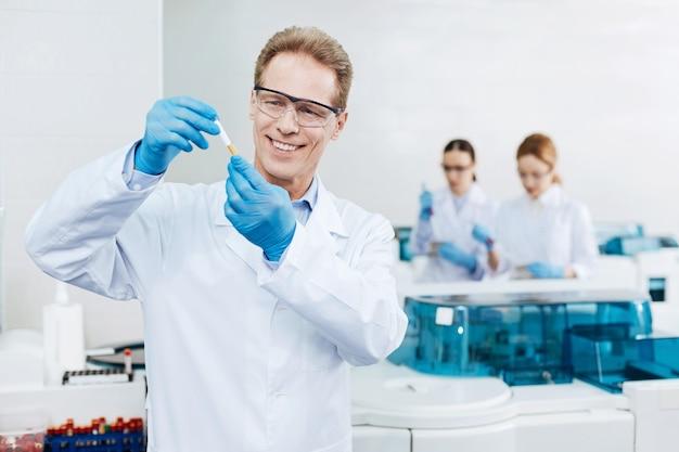 Ten mucho cuidado. practicante encantado positivo con gafas protectoras levantando ambas manos mientras revisa el tubo de ensayo