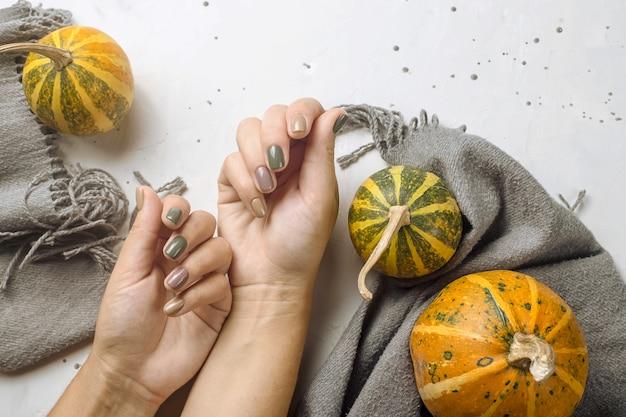 Tendencia de manicura en colores otoñales en una mesa gris junto a calabazas y una bufanda gris