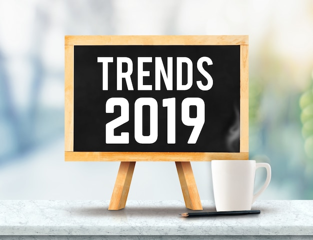 Tendencias 2019 en pizarra con caballete en mesa de mármol con sol y desenfoque árbol verde bokeh ba