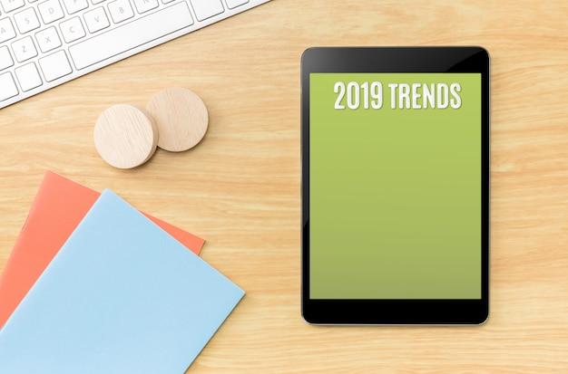 Tendencias 2019 en tableta de pantalla verde con notebook y teclado en mesa