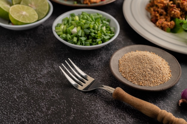 Tenedor, arroz tostado, cebolletas picadas y lima cortada por la mitad sobre un piso de cemento negro.